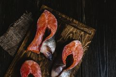 Sliced fresh salmon fish on wooden cutting board with sackcloth on rustic table. Top view of sliced fresh salmon fish on wooden cutting board with sackcloth on Royalty Free Stock Photo