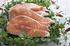Sliced fresh salmon. A platter with sliced fresh salmon and ingredients to cook it on the table of the kitchen Stock Photo