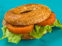 Sliced Fresh Tomato and Lettuce Salad Sesame Seeded Bagel. Tomato and Lettuce Salad Sesame Seeded Bagel Against A Blue Background Royalty Free Stock Photography
