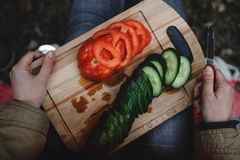 Sliced fresh tomatoes and cucumbers on the board. Hands hold the knife stock image