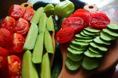 Sliced ??fresh vegetables. On the boards are sliced ??cucumbers and tomatoes, and peppers back Royalty Free Stock Image