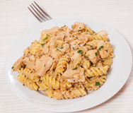Sliced fried chicken fillet in a creamy and mustard sauce. with fusilli pasta Stock Photo