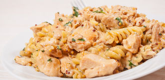 Sliced fried chicken fillet in a creamy and mustard sauce. with fusilli pasta Royalty Free Stock Image