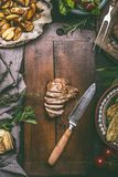 Sliced fried pork meat and kitchen knife  on cutting board with baked potatoes. On rustic table, top view Royalty Free Stock Photography