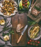 Sliced fried pork meat and kitchen knife on cutting board with baked potatoes, zucchini and salad. On rustic table, top view Stock Photography