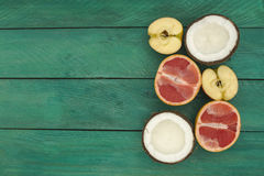 Sliced fruit - grapefruit, coconut, apple, on a wooden background. Royalty Free Stock Images