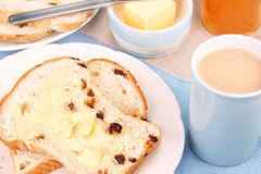Sliced fruit loaf with sultanas and a cup of tea with milk. Selective focus Royalty Free Stock Photography