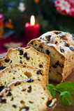 Sliced fruitcake with raisins and mint leaf on chr. Sliced christmas fruitcake with raisins and mint leaf on christmas background Royalty Free Stock Images
