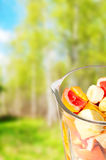 Sliced Fruits arranged in plastic cup with spring green background royalty free stock photo