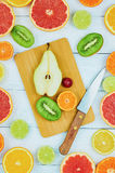 Sliced fruits. Oranges, limes, grapefruits, tangerines, pear, kiwi and lemons. Over wood table background with copy space. Top view Stock Photos
