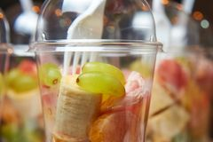 Sliced fruits in plastic cup. healthy food catering. Fruit salad. Fitness food. Close up stock images