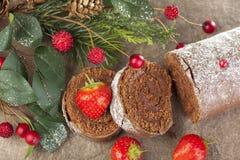 Sliced glaserade chokladyulejournalen med jordgubbar på jul Royaltyfri Fotografi