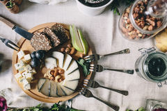 Sliced goat cheese with Dorblu with slices of bread, pears, grapes on a wooden plate. Nearby lie the fork, butter knife, a glass jar with hazelnuts. Top view Stock Photos