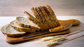 Sliced grain bread on a wooden Board. With ears of wheat royalty free stock photos