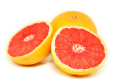 Sliced Grapefruit. Two grapefruits, one sliced into two halves and one in the background Royalty Free Stock Photo