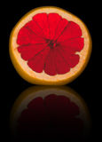 Sliced grapefruit. Isolated on black with reflection Stock Photos