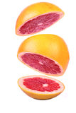 Sliced grapefruit. Cut into three parts grapefruit hovers in the air Royalty Free Stock Photography