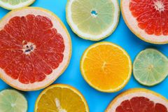 Sliced grapefruit, lemon, lime and orange on blue wooden table,. Flat lay. Juicy citrus slices summer background stock images