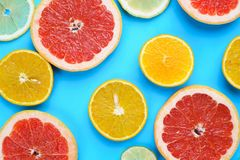 Sliced grapefruit, lemon, lime and orange on blue wooden table,. Flat lay. Juicy citrus slices summer background royalty free stock photography