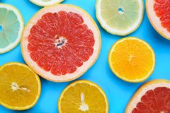 Sliced grapefruit, lemon, lime and orange on blue wooden table,. Flat lay. Juicy citrus slices summer background royalty free stock photos