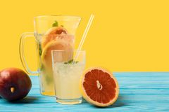 Sliced grapefruit, ripe mango and fresh cold summer drink in glass and jug on turquoise wooden table royalty free stock photo