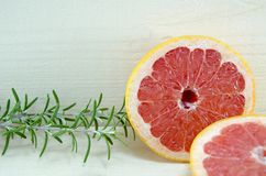 Sliced grapefruit with rosemary branch on a table Stock Images
