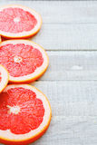 Sliced ​​grapefruit on wooden table Stock Image