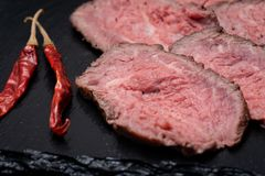Sliced Grass Fed Juicy Corn Roast Beef garnished with dried Red Chile De Arbol Pepper on black natural stone. Background stock photo
