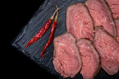 Sliced Grass Fed Juicy Corn Roast Beef garnished with dried Red Chile De Arbol Pepper on black natural stone. Background royalty free stock photos