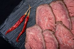 Sliced Grass Fed Juicy Corn Roast Beef garnished with dried Red Chile De Arbol Pepper on black natural stone. Background royalty free stock photo