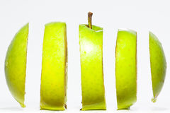 Sliced green apple. A green apple impossibly sliced against a white background Stock Images