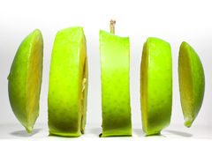 Sliced green apple. A green apple impossibly sliced against a white background Royalty Free Stock Photography
