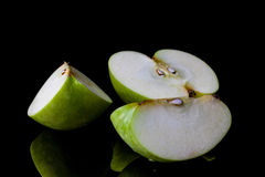 Sliced green apple on black from side Royalty Free Stock Images