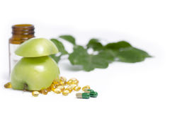 SLICED GREEN APPLE WITH CAPSULES AND MEDICINE BOTTLE. Sliced green apple with gold capsules and open medicine bottle on white background royalty free stock photos