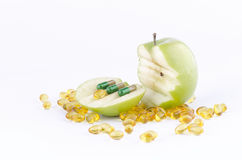 SLICED GREEN APPLE WITH CAPSULES 2. Three capsules on a sliced green apple on white background with gold capsules royalty free stock images