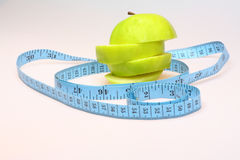 Sliced green apple healthy eating. Single  green apple sliced up plus blue tape measure Royalty Free Stock Photography