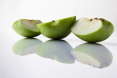 Sliced green apple from side with reflection on white Royalty Free Stock Photography