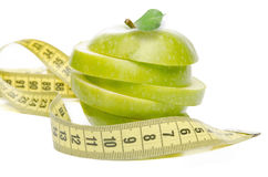 Sliced Green Apple and tape measure Royalty Free Stock Photos