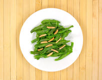 Sliced green beans with almonds on a white plate Stock Images