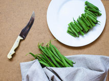 Sliced green beans on a white plate and a bunch of green beans Stock Photography