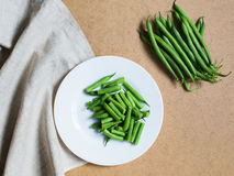 Sliced green beans on a white plate and a bunch of green beans Royalty Free Stock Images