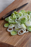 Sliced green leek on wooden chopping board Royalty Free Stock Images