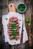 Sliced grilled barbecue beef steak with green chimichurri sauce Royalty Free Stock Photos