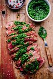 Sliced grilled barbecue beef steak with green chimichurri sauce Stock Photo