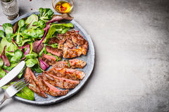Sliced grilled beef steak with green leaves salad on rustic plate with cutlery. stock images