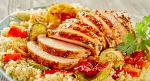 Sliced grilled chicken breasts on couscous. Sliced grilled chicken breasts on vegetable couscous with zucchini, peppers and tomatoes for a healthy vegetarian Stock Photos