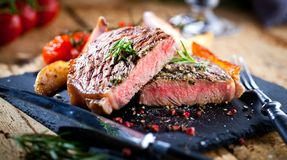 Sliced grilled meat barbecue steak Striploin with knife and fork carving set on black stone slate. royalty free stock images