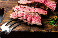 Sliced grilled medium rare beef steak served on wooden board Barbecue, bbq meat beef tenderloin. Top view, slate