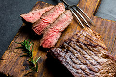 Sliced grilled medium rare beef steak served on wooden board Barbecue, bbq meat beef tenderloin. Top view, slate background