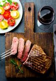 Sliced grilled medium rare beef steak served on wooden board Barbecue, bbq meat beef tenderloin. Top view, slate background stock photo